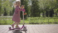 Adorable little funny girl in pink dress riding a scooter in the park. Camera following the child 52209275