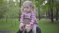 Handsome blond boy playing with her cute sister in the park holding her on his shoulders. The boy 52209401