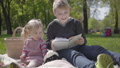 Teenage blond boy sitting on blanket in the park reading the book to her little sister in pink dress 52209636