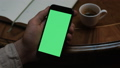 Man holds a modern smartphone with green screen display in a cafe with a cup of coffee on the table. 52212987