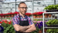 Portrait of happy male professional farmer posing in greenhouse looking at camera medium close-up 52983724