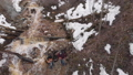 Aerial view of people playing guitars in a ravine near the small and dirty mountain stream in the 52996573