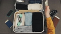 Woman's hands packing suitcase for a journey on the bed at home. Travel preparations. 53067921