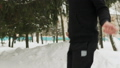 Young guy in a black sports suit, performing exercises, jumping rope in a snow-covered Park outdoors 53221474