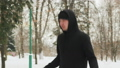 Young guy in a sports suit in black, doing exercises, jumping rope in a snow-covered Park outdoors 53221509