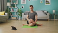 A young man studies yoga using instructions on a tablet 53234127