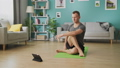 A young man studies yoga using instructions on a tablet 53234170