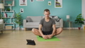 Young man following the instructions on the tablet and do the asana 53234187