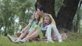 Portrait senior woman kissing and hugging cute granddaughters sitting on the grass under the tree in 53307880