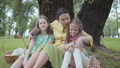 Portrait cute mature woman kissing her two cute granddaughters sitting on the grass under the tree 53307928