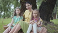 Mature woman sitting on the grass under the tree in the park with two cute granddaughters, looking 53307955