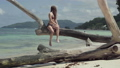 Seychelles. Praslin Island. Pretty slim attractive young woman sitting on the tree trunk at the 53355689