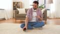 man in headphones meditating in lotus pose at home 53626009