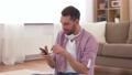 man in headphones meditating in lotus pose at home 53626014