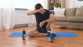 man with fitness tracker drinking water at home 53626017