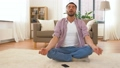man in headphones meditating in lotus pose at home 53626019