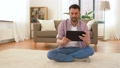 man with tablet computer meditating at home 53626020