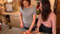 台所で話しながらフランスパンを切る日本人女性 53794189