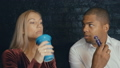 Young Couple talking in bar. Dating. Caucasian woman drinking coffee and black man smoking vape at 54032650
