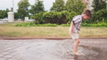 Children having fun and barefoot playing in puddle after rain in park 54168591