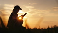 The farmer uses the tablet, working in his field at sunset 54195618