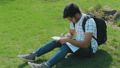 Student with Glasses and Backpack Doing Homework Sitting on the Lawn in the City Park 54250635