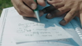 Close-Up,the Hands of an Indian Student with A Pen Recorded on a Sheet of Paper Notes from the Book 54250636