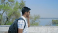 Indian Guy with Glasses and backpack Talking on the Phone, Walking in the Park against the River 54252345