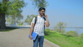 Indian Student with Glasses with Notebooks in Hand Talking on the Phone on the Way to University 54252633