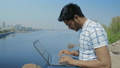 Close-Up, Indian Student in Glasses Working on a Laptop, Sitting on the River Bank 54254064