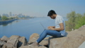 Handsome Indian Guy in Glasses is Working on a Laptop, Sitting on a Stone on the River Bank 54254065