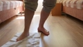 Man washes the floor in the room with his foot 54275562