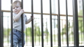 Boy child clings to the fence 54284540