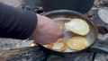 Tourist is cooking pancakes in frying pan over the fire. Campfire in the woods. 54287072