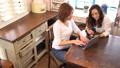 楽しそうにパソコンとスマホを操作しながら話す2人の女性 54317133