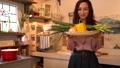 キッチンでたくさんの野菜を抱えてカメラ目線で微笑む女性 54317196