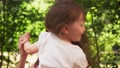 Happy mother hugs adorable little daughter and whirls with her in sunny park 54325662