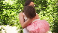 Mother hugs adorable baby and whirls with her in sunny summer park 54325667