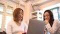 ノートパソコンを見ながら話をする2人の日本人女性 54357131