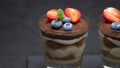 Classic tiramisu dessert with blueberries and strawberries in a glass on stone serving board 54362915