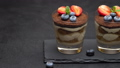 Classic tiramisu dessert with blueberries and strawberries in a glass on stone serving board 54362923
