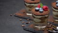 Classic tiramisu dessert with blueberries and raspberries in a glass on stone serving board 54366704