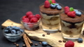 Classic tiramisu dessert with blueberries and raspberries in a glass on wooden cutting board 54368703