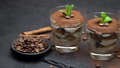 Classic tiramisu dessert in a glass on stone serving board on dark concrete background 54373460