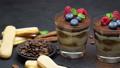 tiramisu dessert with blueberries and raspberries in a glass and savoiardi cookies 54416241