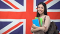 Cheerful Asian woman standing against British flag 54460795