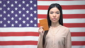 Confident Asian woman showing passport against USA 54460800