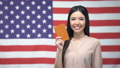 Adorable female showing passport against USA flag 54460801