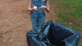 Little girl throw paper in waste container in park 54465740