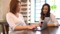 テーブルの上でパソコンを操作しながら話をする2人の日本人女性 54489250